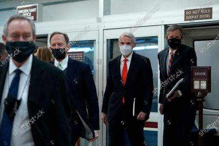 From left, Sen. Mike Crapo, R-Idaho, Sen. Pat Toomey, R-Pa., Sen. Rob Portman, R-Ohio, and Sen. Steve Daines, R-Mont., walk off of the Senate subway on Capitol Hill in Washington, on the fourth day of the second impeachment trial of former President Donald Trump