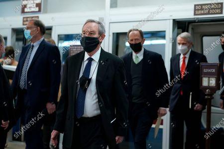 From left, Sen. John Boozman, R-Ark., Sen. Mike Crapo, R-Idaho, Sen. Pat Toomey, R-Pa., and Sen. Rob Portman, R-Ohio, walk off of the Senate subway on Capitol Hill in Washington, on the fourth day of the second impeachment trial of former President Donald Trump
