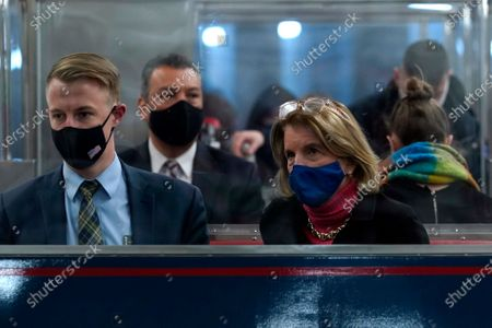 Sen. Shelley Moore Capito, R-W.Va., front right, and Sen. Alex Padilla, D-Calif., second from left, ride the Senate subway on Capitol Hill in Washington, on the fourth day of the second impeachment trial of former President Donald Trump