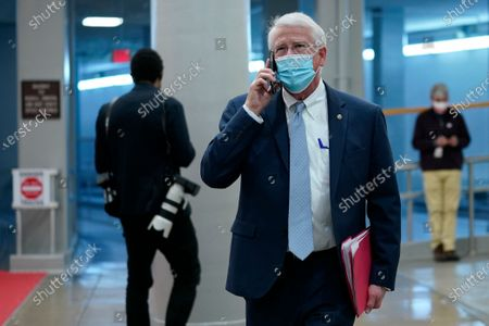 Sen. Roger Wicker, R-Miss., talks on a phone as he walks on Capitol Hill in Washington, on the fourth day of the second impeachment trial of former President Donald Trump