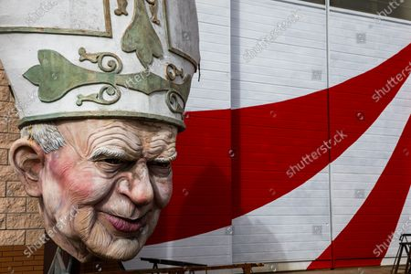 Stock Photo of View of Pope John Paul II (Wojtyla) statue insidef the Cittadella complex, composed of 16 warehouses and a big central elliptical square. The Carnival of Viareggio was born in 1873 and nowadays is the largest Italian folk event. The rules for the prevention of Covid disease this year prevent the traditional parade of floats on Mardi Gras. The Cittadella of Viareggio in the days of the carnival is the nodal center of important events, but this year the sixteen Hangars, where the allegorical floats are built, are full of activity even though the parades have been postponed due to the pandemic of Covid-19.