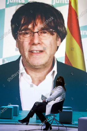 Catalan pro-independence party Junts per Catalunya (JxCat)'s presidential candidate Laura Borras (R) reacts as former Catalan President Carles Puigdemont (on screen) delivers a speech via video conference during an electoral rally at the closing day of the Catalan presidential election campaign, in Barcelona, Catalonia, Spain, 12 February 2021. Catalonia will hold regional elections on 14 February 2021.