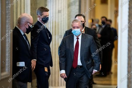 WASHINGTON, DC - FEBRUARY 12: Sen. Lindsey Graham, R-S.C., walks with Jason Miller to a meeting room for lawyers of former President Donald Trump on the fourth day of the Senate Impeachment trials for former President Donald Trump on Capitol Hill in Washington, DC.
