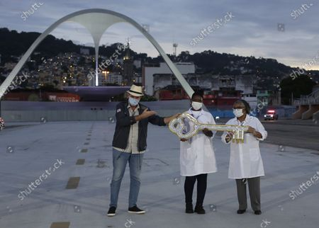 After receiving the key of the city from Carnival King Momo, Mayor Eduardo Paes, left center, passed the key to healthcare workers at a lighting ceremony in the Sambadrome in honor of the victims of COVID-19, a ceremony that would have normally marked the official start of Carnival but has been cancelled due to the new cornavirus pandemic, in Rio de Janeiro, Brazil