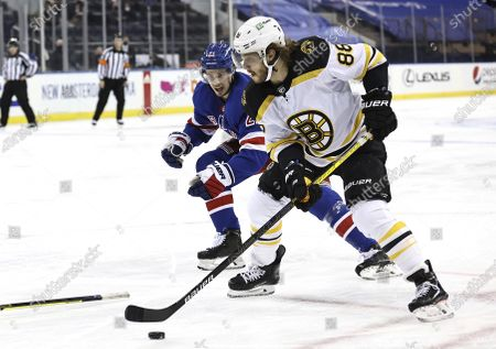 Boston Bruins' David Pastrnak (88) heads for the net as New York Rangers' Brett Howden (21) defends in the first period of an NHL hockey game, in New York