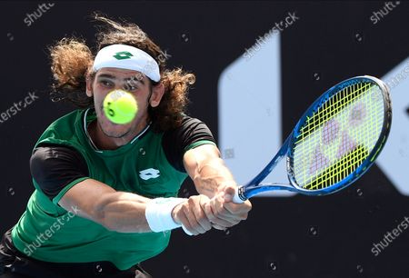 South Africa's Lloyd Harris hits a backhand return to United States' Mackenzie McDonald during their third round match at the Australian Open tennis championship in Melbourne, Australia