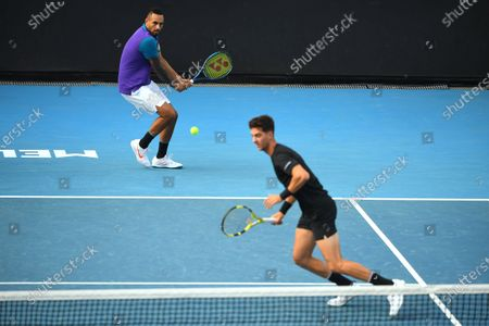 Australia's Nick Kyrgios (L) hits the ball as Australia's Thanasi Kokkinakis in action during their first Round Men's doubles match against South Africa's Lloyd Harris and Austria's Julian Knowle at the Australian Open grand slam tennis tournament at Melbourne Park in Melbourne, Australia, 13 February 2021.