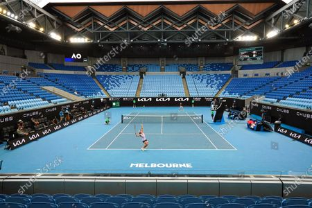 Stock Photo of Ashleigh Barty (front) of Australia in action during her women's singles third round match against Ekaterina Alexandrova (back) of Russia at the Australian Open Grand Slam tennis tournament in an empty Margaret Court Arena at Melbourne Park in Melbourne, Australia, 13 February 2021.