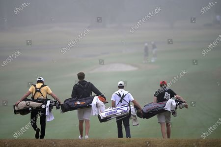 Harrison Ott, left, of Vanderbilt, Rhys Nevin-Wharton, second from left, of Tennessee, Fred Biondi, of Florida, and Connor Creasy, of Georgia, walk in the fog on the first fairway after hitting their tee shots during an NCAA golf tournament on Friday, in Gainesville, Fla