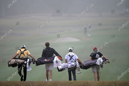 Harrison Ott, left, of Vanderbilt, Rhys Nevin-Wharton, second from left, of Tennessee, Fred Biondi, of Florida, and Connor Creasy, of Georgia, walk in the fog on the first fairway after hitting their tee shots during an NCAA golf tournament, in Gainesville, Fla
