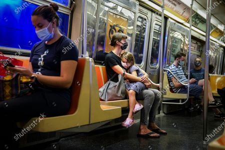 Stock Picture of This photo from, shows riders on a subway train wearing protective masks due to COVID-19 concerns in New York. The Metropolitan Transportation Authority on Friday launched a campaign that has celebrities including Jerry Seinfeld, Whoopi Goldberg, and Awkwafina making the announcements heard at subway stations, on trains, and buses