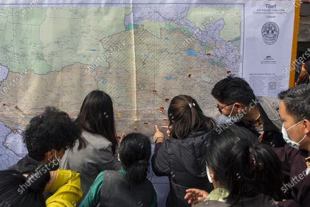 Exile Tibetans pin miniature Tibetan flags on their hometowns on a map of the Tibetan region at a street event to mark the day when the 13th Dalai Lama declared Tibet an independent state in 1913, in Dharmsala, India, . Tibetans mark this day as Tibetan Independence Day