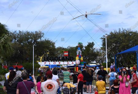 Stock Image of Spectators watch as aerialist Nik Wallenda walks a high wire for 600 feet between two buildings at the LEGOLAND Florida Resort on February 12, 2021 in Winter Haven, Florida. Wallenda performed the 60-foot high stunt with a balancing pole decorated with plastic LEGO bricks as part of the theme parks 10-year anniversary celebration.