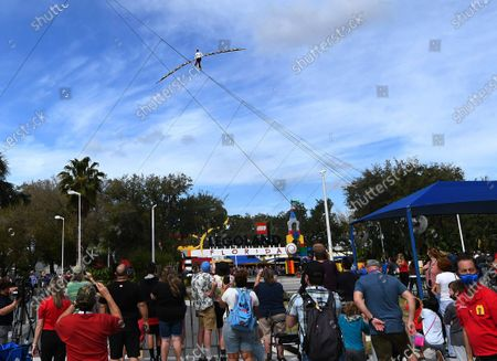 Stock Picture of Spectators watch as aerialist Nik Wallenda walks a high wire for 600 feet between two buildings at the LEGOLAND Florida Resort on February 12, 2021 in Winter Haven, Florida. Wallenda performed the 60-foot high stunt with a balancing pole decorated with plastic LEGO bricks as part of the theme parks 10-year anniversary celebration.