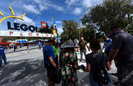 Aerialist Nik Wallenda prays in a circle with his family and crew members at the entrance to the LEGOLAND Florida resort before walking a high wire for 600 feet between two buildings at the attraction on February 12, 2021 in Winter Haven, Florida. Wallenda performed the 60-foot high stunt with a balancing pole decorated with plastic LEGO bricks as part of the theme parks 10-year anniversary celebration.