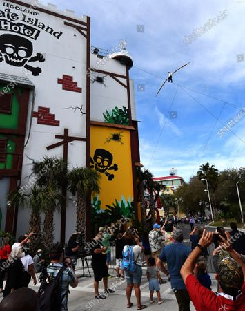 Aerialist Nik Wallenda approaches the roof of the Pirate Island Hotel after walking a high wire for 600 feet at the LEGOLAND Florida Resort on February 12, 2021 in Winter Haven, Florida. Wallenda performed the 60-foot high stunt with a balancing pole decorated with plastic LEGO bricks as part of the theme parks 10-year anniversary celebration.