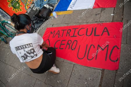 """A demonstrator from the Universidad Pedagogica in Bogota, writes a banner reading """"Zero tuition"""" """"Matricula Cero, as they demonstrate for the adquisition of a free tuition to its students after the novel Coronavirus pandemic caused an economic recession, in Bogota, Colombia on February 12, 2020."""