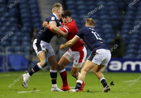 Louis Rees-Zammit of Wales is tackled by Duhan van der Merwe and Chris Harris of Scotland.