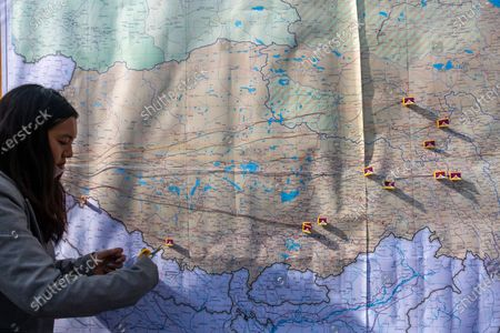 An exile Tibetan activist cuts a thread connecting a miniature Tibetan flag on a map of the Tibetan region at a street event to mark the day when the 13th Dalai Lama declared Tibet an independent state in 1913, in Dharmsala, India, . Tibetans mark this day as Tibetan Independence Day