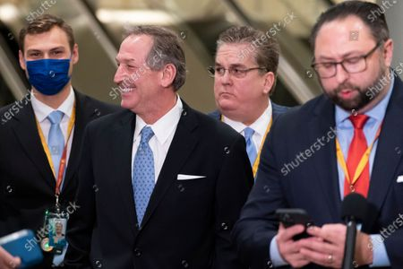 Michael van der Veen, second from left, an attorney from former President Donald Trump, smiles at reporters on Capitol Hill after the Senate acquitted Trump in his second impeachment trial in the Senate at the U.S. Capitol in Washington, . Trump was accused of inciting the Jan. 6 attack on the U.S. Capitol, and the acquittal gives him a historic second victory in the court of impeachment. Jason Miller, former senior advisor to 2020 Trump campaign, stands at right