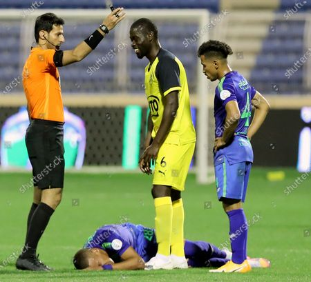 Saudi referee Majed Al Shamrani (L) awards a foul against Al-Ain's player Badou Ndiaye (2-R) as Al-Fateh's player Sofiane Bendebka (down) lies injured on the ground during the Saudi Professional League soccer match between Al-Fateh and Al-Ain at Prince Abdullah bin Jalawi Stadium, in Al-Hasa, Saudi Arabia, 13 February 2021.