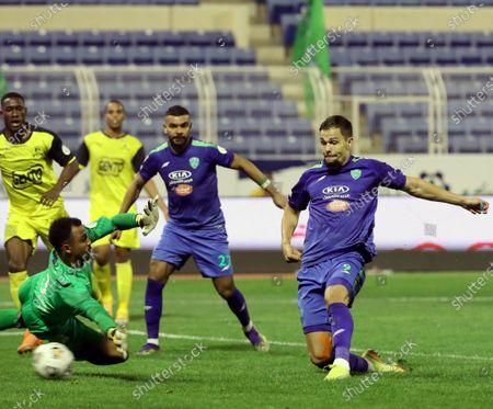 Al-Fateh's player Mitchell Te Vrede (R) scores a goal against Al-Ain's goalkeeper Ameen Bokhari (L- down) during the Saudi Professional League soccer match between Al-Fateh and Al-Ain at Prince Abdullah bin Jalawi Stadium, in Al-Hasa, Saudi Arabia, 13 February 2021.