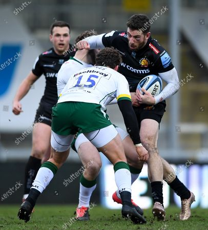 Stock Image of Alex Cuthbert of Exeter Chiefs is challenged by Theo Brophy Clews of London Irish and James Stokes of London Irish