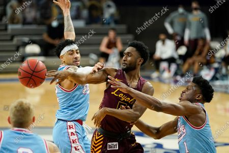 Loyola of Chicago guard Keith Clemons, center, passes between Drake guard Roman Penn, left, and guard Joseph Yesufu, right, during the first half of an NCAA college basketball game, in Des Moines, Iowa