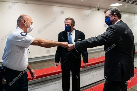 A Capitol Hill employee fist-bumps Bruce Castor, right, and Michael van der Veen, the defense attorneys for Donald Trump.