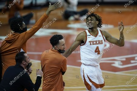 Texas forward Greg Brown (4) celebrates a play with head coach Shaka Smart and teammates during the second half of an NCAA college basketball game against TCU, in Austin, Texas