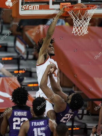 Texas forward Greg Brown (4) scores over TCU center Kevin Samuel (21) during the second half of an NCAA college basketball game, in Austin, Texas