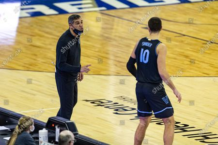 Villanova head coach Jay Wright, left, gives forward Cole Swider (10) instructions before Swider goes in to play against Creighton in the second half during an NCAA college basketball game, in Omaha, Neb