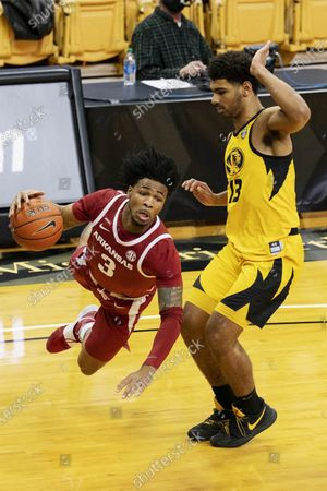 Arkansas' Desi Sills, left, is fouled by Missouri's Mark Smith, right, during the first half of an NCAA college basketball game, in Columbia, Mo