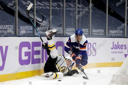 Boston Bruins left wing Anders Bjork (10) falls to the ice in front of New York Islanders center Anders Lee (27) during the first period of an NHL hockey game, in Uniondale, N.Y