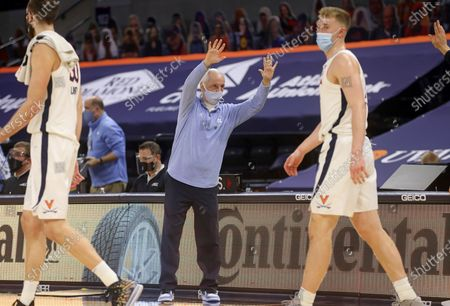 North Carolina coach Roy Williams waves goodbye to the Virginia coaching staff after an NCAA college basketball game, in Charlottesville, Va
