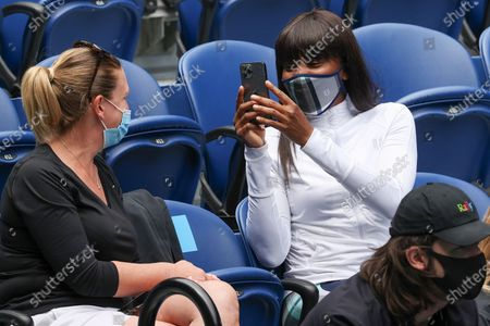 Venus Williams, right, takes a photo of a friend as she watches her sister Serena on Rod Laver Arena during her fourth round match against Aryna Sabalenka at the Australian Open tennis championship in Melbourne, Australia