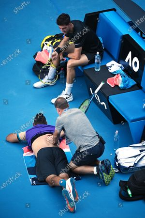 Thanasi Kokkinakis of Australia (R) looks on as Nick Kyrgios receives treatment during their second Round Men's doubles match against Lukasz Kubot of Poland and Wesley Koolhof of the Netherlands on Day 7 of the Australian Open at Melbourne Park in Melbourne, Australia, 14 February 2021.