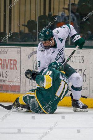 Stock Image of Bemidji State defenseman Brad Johnson (18) battles with Northern Michigan forward Andre Ghantous (11) for the puck during an NCAA hockey game, in Bemidji, Minn