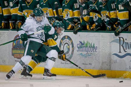 Eric Martin (11) battles with Northern Michigan forward David Keefer (7) for the puck during an NCAA hockey game, in Bemidji, Minn