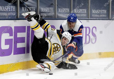Boston Bruins left wing Anders Bjork (10) falls to the ice battling for the puck with New York Islanders center Anders Lee during the first period of an NHL hockey game, in Uniondale, N.Y