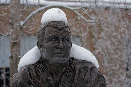 The statue of former Washington NCAA college football coach Jim Owens wears a coating of snow, in Seattle. Winter weather was expected to continue through the weekend in the region