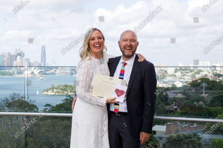 Sydney couple Tahi Cody (L) and Matt Hayward react during their wedding at Taronga Zoo on Valentine's Day in Sydney, New South Wales (NSW), Australia, 14 February 2021. The ceremony was the first of 40 micro weddings to be conducted by the NSW Registry of Birth, Deaths and Marriages at the zoo.