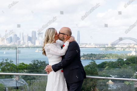 Sydney couple Tahi Cody (L) and Matt Hayward kiss during their wedding ceremony at Taronga Zoo on Valentine's Day in Sydney, New South Wales (NSW), Australia, 14 February 2021. The ceremony was the first of 40 micro weddings to be conducted by the NSW Registry of Birth, Deaths and Marriages at the zoo.