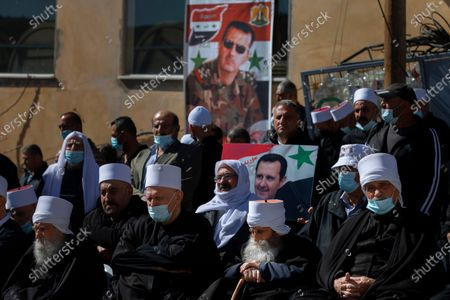 Stock Photo of Druse supporters of Syrian President Bashar Assad display display pictures of him during a rally close to the Syrian border demanding the return of the Golan Heights, captured by Israel in 1967, in Majdal Shams, Golan Heights, . The annual demonstration is in protest of the 1981 Israeli law in which the Jewish state annexed the strategic plateau it captured from Syria during the 1967 Arab-Israeli war