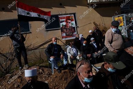 Druse supporters of Syrian President Bashar Assad wave a Syrian flag and display a picture of him during a rally close to the Syrian border demanding the return of the Golan Heights, captured by Israel in 1967, in Majdal Shams, Golan Heights, . The annual demonstration is in protest of the 1981 Israeli law in which the Jewish state annexed the strategic plateau it captured from Syria during the 1967 Arab-Israeli war