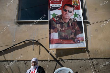 Druze woman sets next to a picture of the Syrian president Bashar al-Assad during the  the 39th anniversary of the Druze general strike against the Israeli annexations law of the Golan Heights, in the village of Majdal Shams in the Golan Heights, 14 February 2021.  The Druze of the Golan Heights mark on 14 February their six months' general strike against the Israel annexations law of the Golan in the year 1981, and the imposition on the local population to carry the Israeli identity. Israel occupied the Golan Heights during the six days' war with Syria and Egypt in 1967.