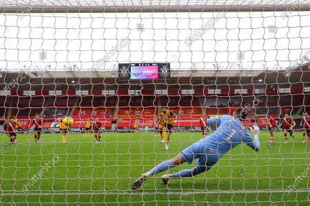 Ruben Neves (C) of Wolverhampton scores the 1-1 equalizer from the penalty spot against Southampton's goalkeeper Alex McCarthy (front) during the English Premier League soccer match between Southampton FC and Wolverhampton Wanderers in Southampton, Britain, 14 February 2021.