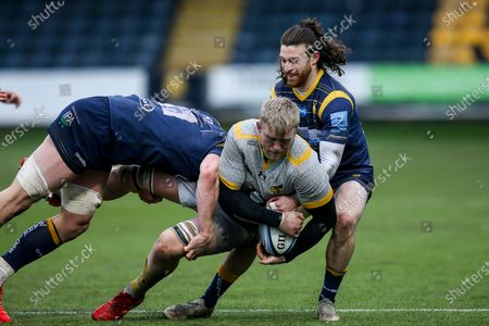 Ben Morris of Wasps is tackled by Ted Hill and Oli Morris of Worcester Warriors