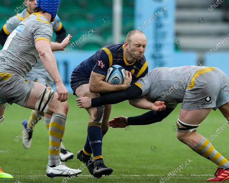 Chris Pennell of Worcester Warriors is tackled by Ben Morris of Wasps