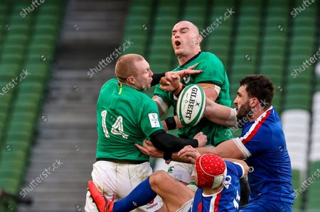 Stock Photo of Ireland vs France. Ireland's Keith Earls and Rhys Ruddock competes in the air with Charles Ollivon of France
